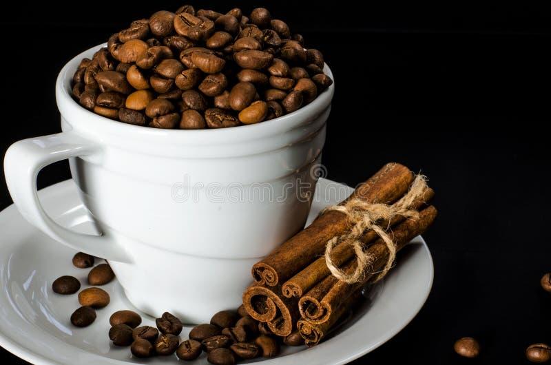 En vit kopp mycket av kaffebönor står på ett vitt tefat, som står på en svart bakgrund royaltyfri bild