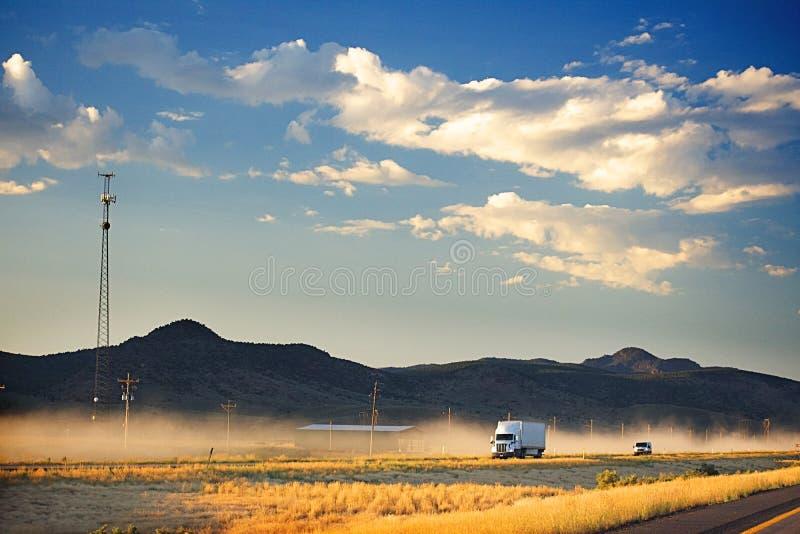 En vit lastbil på en dammig motorväg I bakgrunden är kullar för mörk brunt och ett mörker - blå himmel med fluffiga moln En mobil royaltyfria bilder