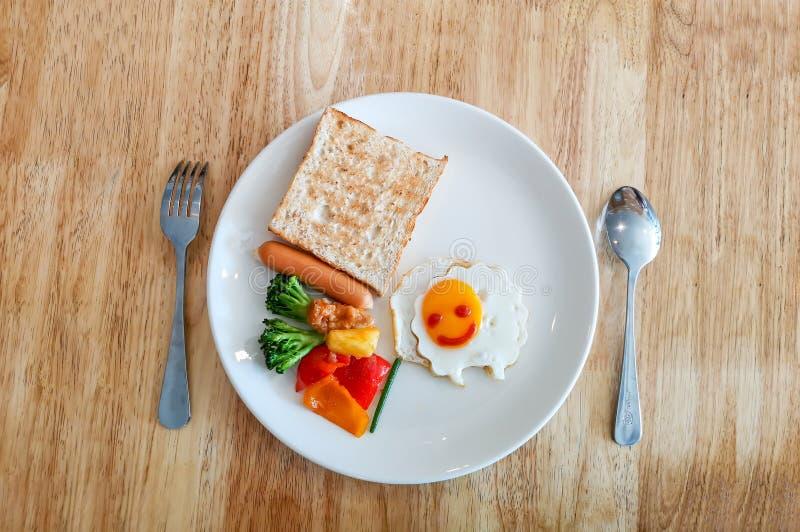 En vit matr?tt av unges frukost som dekoreras med f?r som ler omelett, grillat br?d, korven och gr?nsaken p? tr?tabellen arkivbild