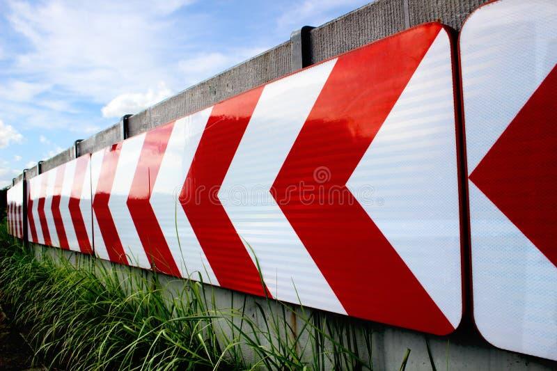 En vit pil som är roterande på ett rött bakgrundsvägmärke royaltyfria foton