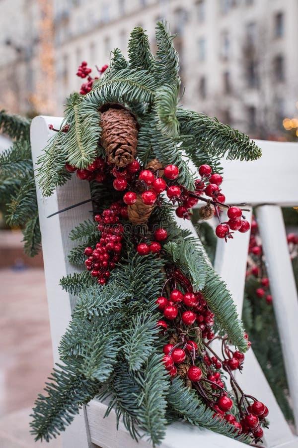En vit träbänk i parkera dekoreras med granfilialer med kottar och röda bär nytt temaår royaltyfri foto