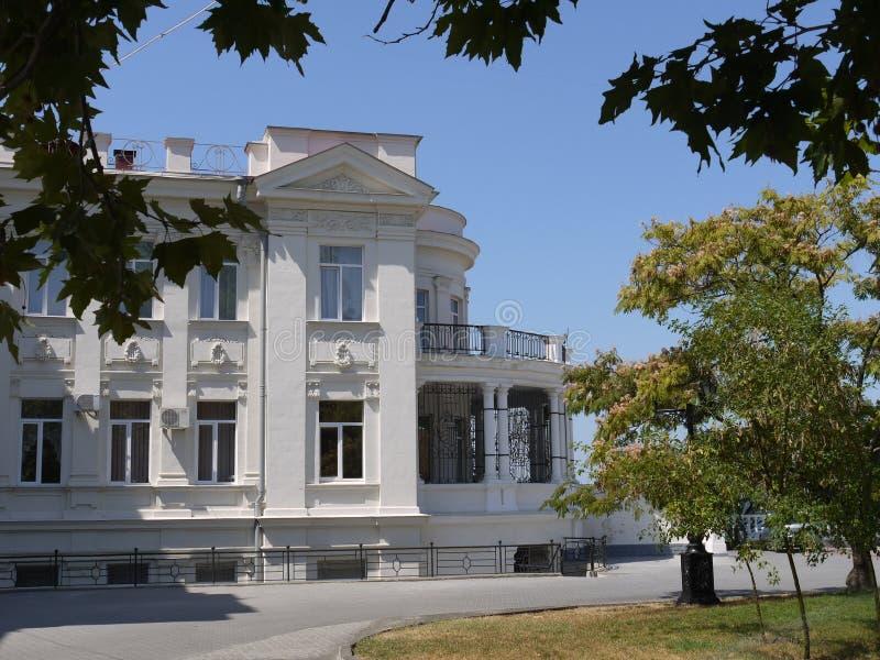 En vit två-berättelse herrgård, ett gods med stuckaturstöpningen, en balkong, träd och en gräsmatta mot bakgrunden av en fördjupn royaltyfria foton