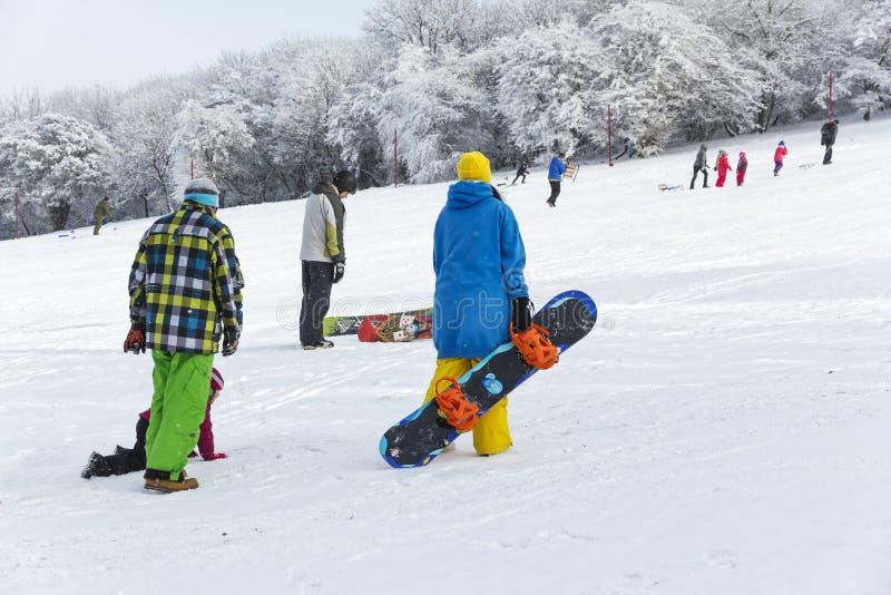 En volwassenen en kinderen die sledding snowboarding stock foto's