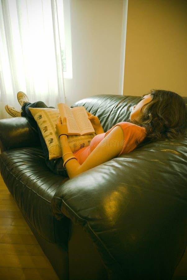 En vrouw die ontspant leest stock afbeeldingen