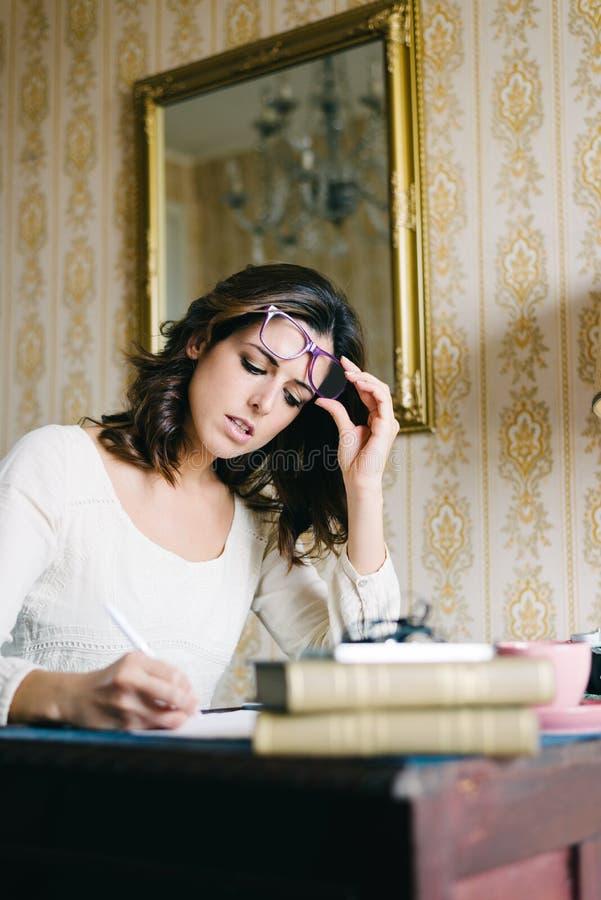 En vrouw die thuis schrijven werken stock foto's