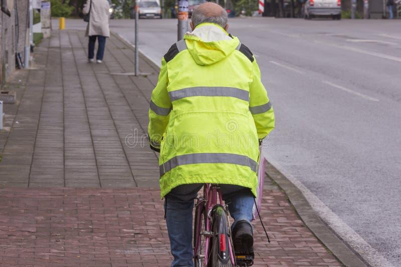 En vuxen cyklist rider en cykel på trottoaren arkivfoton