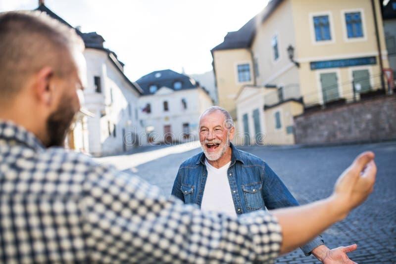 En vuxen hipsterson och hans extatiska höga fader i staden som hälsar royaltyfri foto