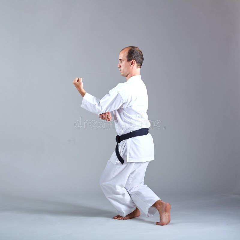 En vuxen idrottsman utbildar formella karateövningar mot en grå bakgrund arkivbild