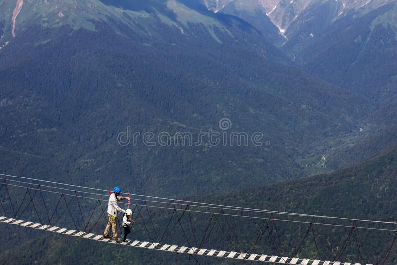 En vuxen människa och en barnflyttning över hänga för bro som är högt i bergen arkivbild
