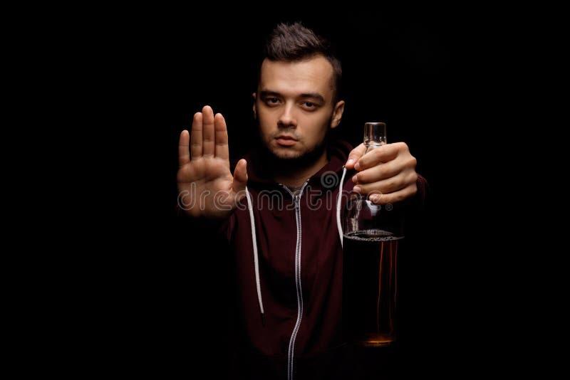 En vuxen man i en röd huv som rymmer en flaska av öl i hans hand och visar ett stopptecken på en svart bakgrund royaltyfri foto