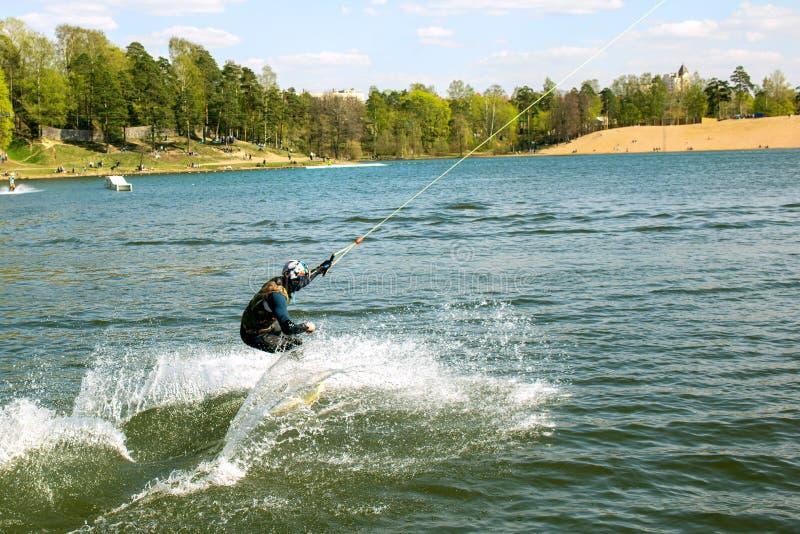 En wakeboarder i flöten för en jumpsuit på en wakeboard som plaskar vatten på sjön parkerar in royaltyfri bild