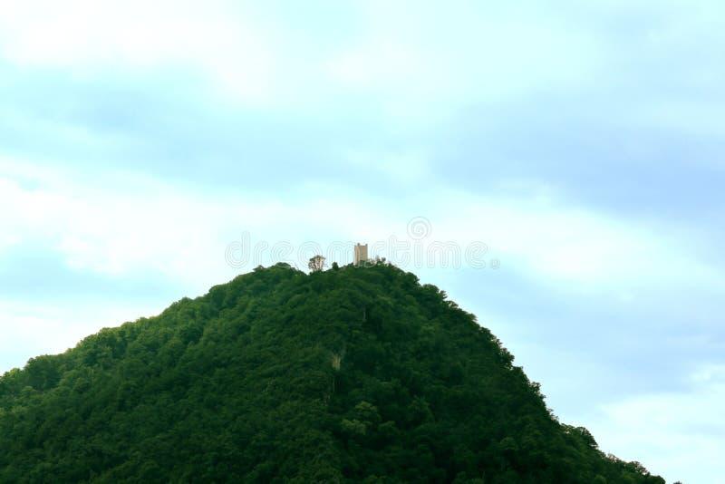 En watchtower på överkanten av ett högväxt grönt berg royaltyfri foto