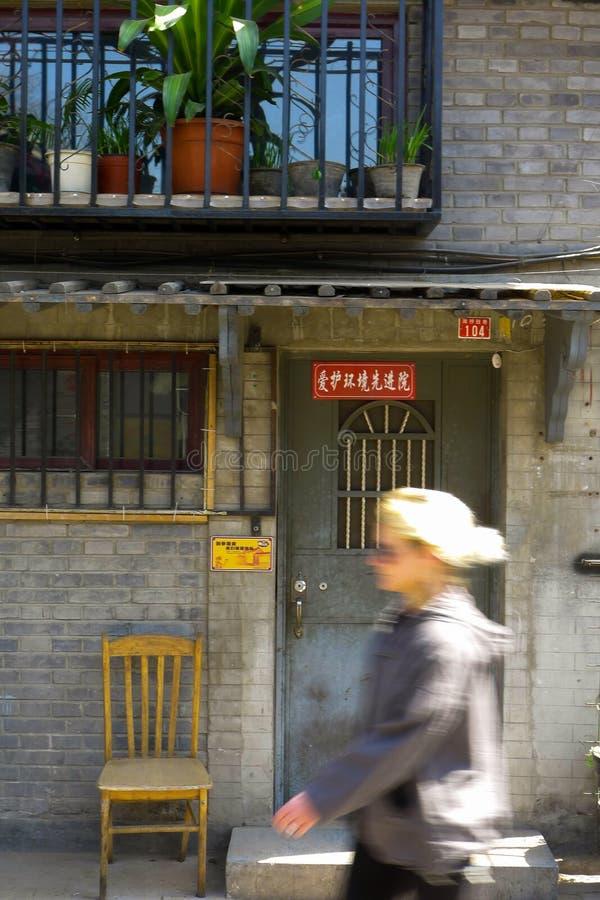 En westerner som går till och med en hutong i Peking royaltyfria bilder
