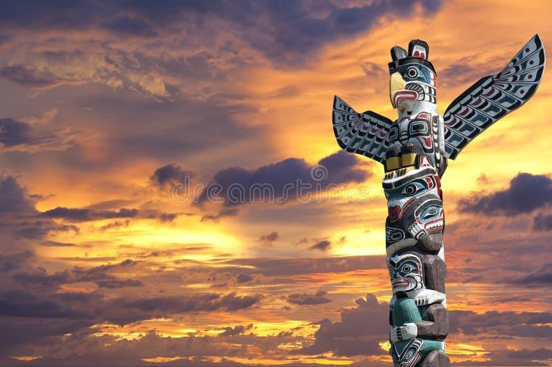 En wood pol för totem i den guld- molniga bakgrunden arkivfoto