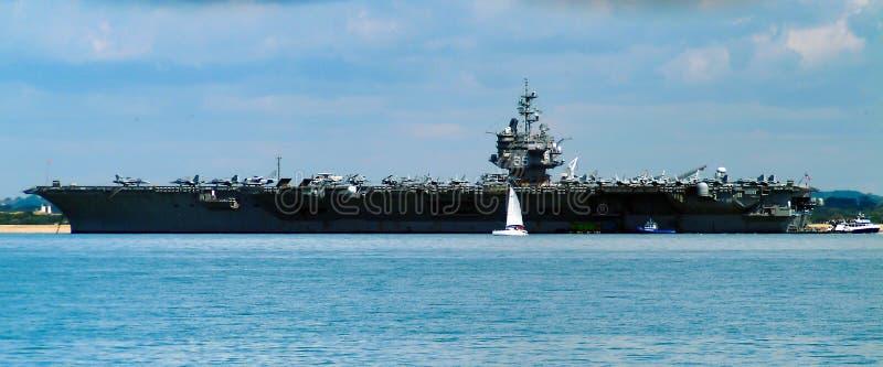 En yacht med seglar upp glidljud förbi den amssive massan av hangarfartyget USS Enterprise i den Portsmouth hamnen arkivbilder