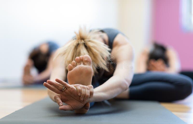 En yoga die uitrekken opleiden zich stock foto's