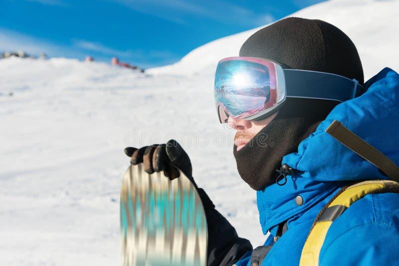 En yrkesmässig snowboarder står med hans snowboard Närbild Stående av ett freerider royaltyfri bild