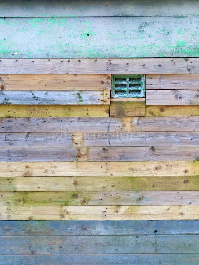 En yttre timmervägg som göras av gamla horisontalred ut plankor som befläckas i olik godis, färgar arkivfoton