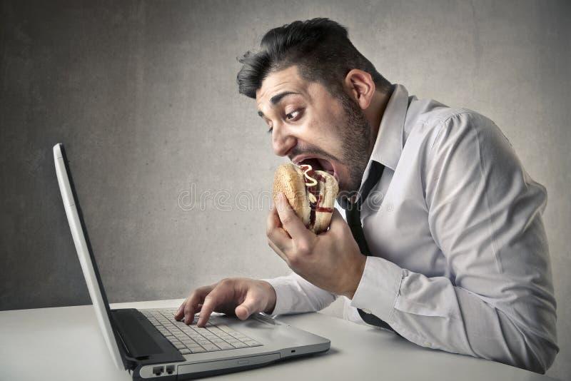 En zakenman die eten werken stock afbeeldingen