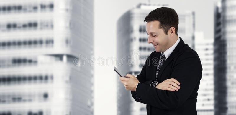 En zakenman Holding Phone While die Gelukkig met Commerciële Stad en Collectieve Gebouwen op Achtergrond glimlachen voelen royalty-vrije stock fotografie