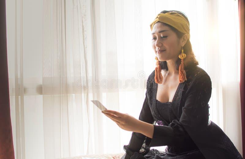 En zigensk kvinna läser tarokkortet i rum royaltyfri fotografi
