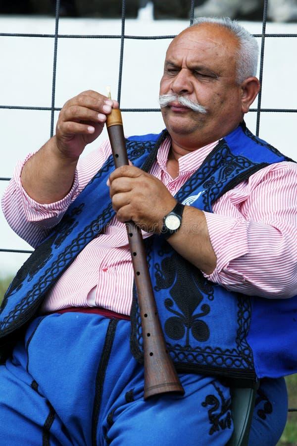 En zigensk musiker justerar hans flöjt på festivalen för brottningen för Kirkpinar turkolja på Edirne i Turkiet arkivfoton