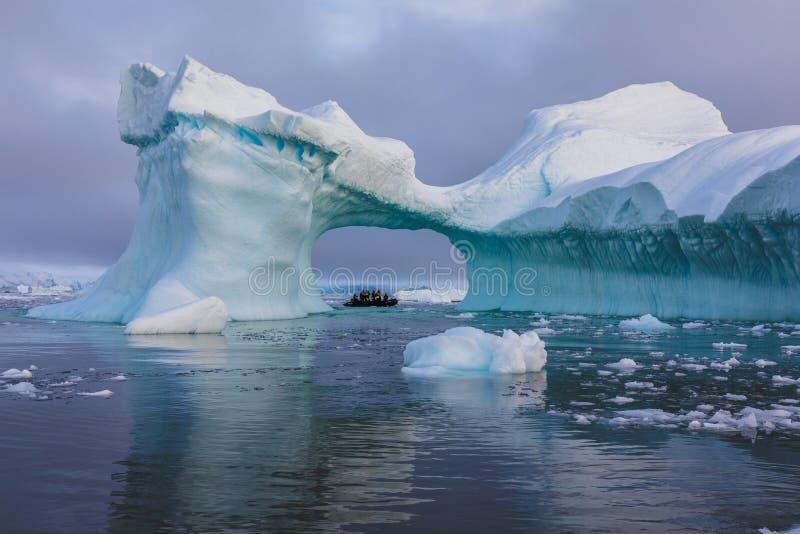 En zodiak mycket av turisten som beskådas till och med en båge i ett stort isberg, Antarktis royaltyfri bild