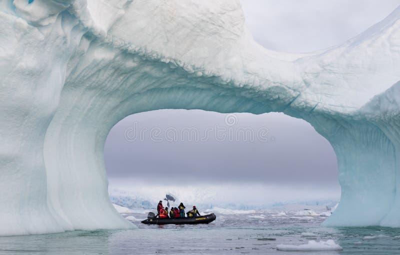 En zodiak mycket av turisten som beskådas till och med en båge i ett stort isberg, Antarktis royaltyfri fotografi