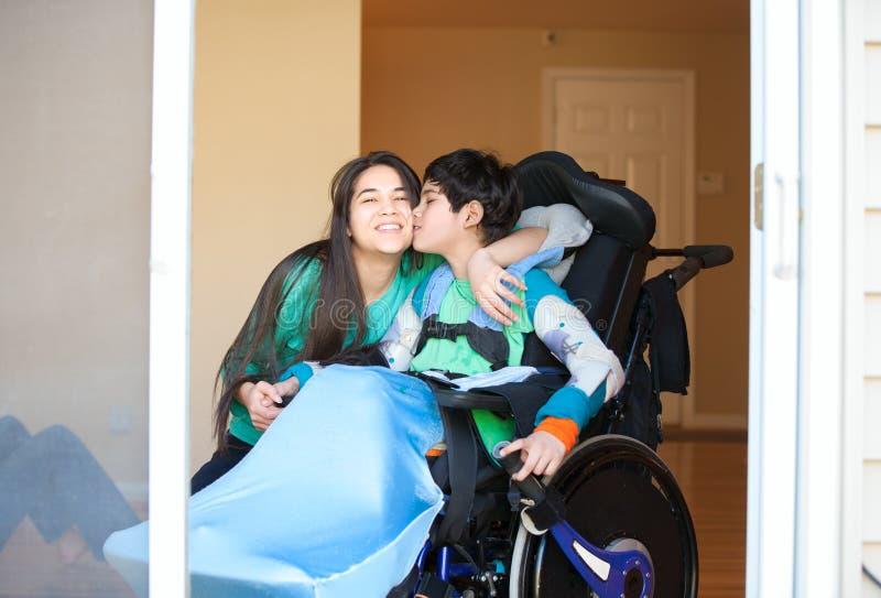 En zuster die gehandicapt weinig broer in rolstoel kussen koesteren stock fotografie
