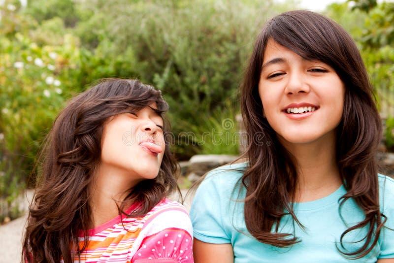 En zusters die samen lachen spelen royalty-vrije stock afbeelding