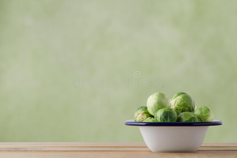 Enamel Baking Pan Filled with Raw Brussel Sprouts. Enamel cooking tin filled with fresh, raw brussel sprouts on light wood plank table. Green background provides royalty free stock images