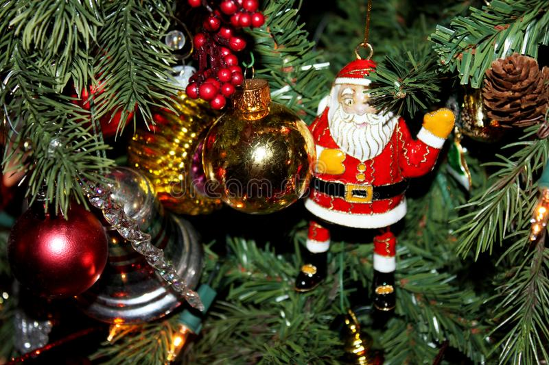Enamel Santa Claus and other ornaments on Traditional Christmas Tree royalty free stock image