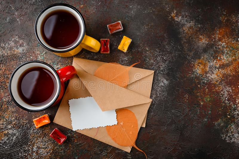 Enameled cup of hot tea. Two colored enamel cups of tea, two envelops, watercolors in cuvettes, , autumn leaves and bumps on a rusty brown background stock photo