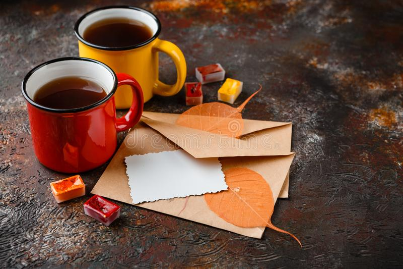 Enameled cup of hot tea. Two colored enamel cups of tea, two envelops, watercolors in cuvettes, , autumn leaves and bumps on a rusty brown background royalty free stock images