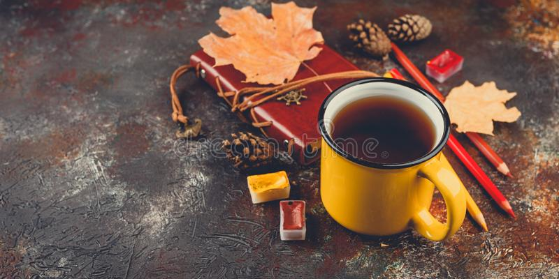 Enameled cup of hot tea. Yellow enamel cups of tea, watercolors in cuvettes, colored pencils, autumn maple leaves and bumps on a brown background stock images