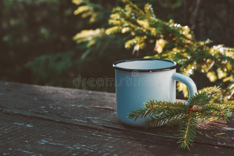 Enamelerad kopp kaffe eller te på träskivor i sommarskog royaltyfria bilder