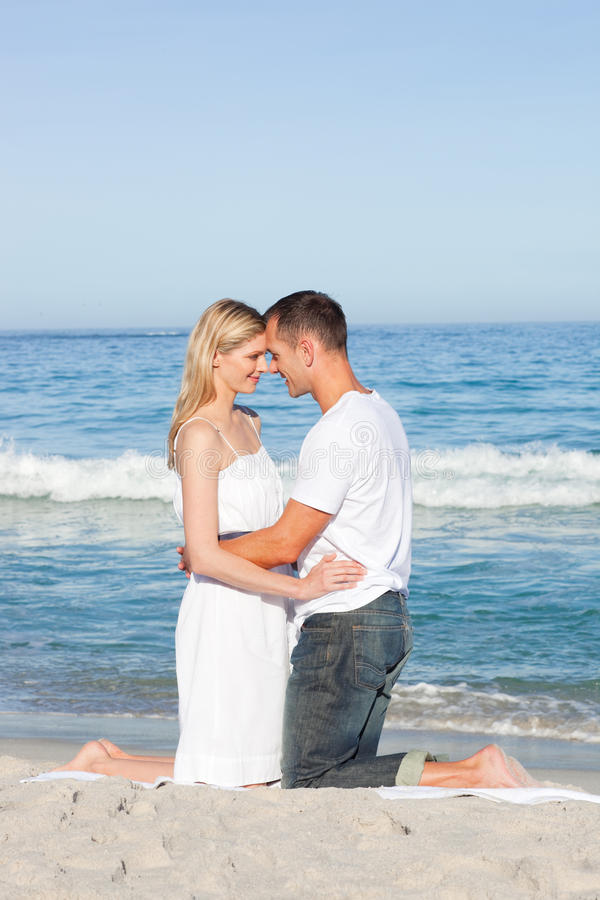 Enamored couple kissing at the shore line
