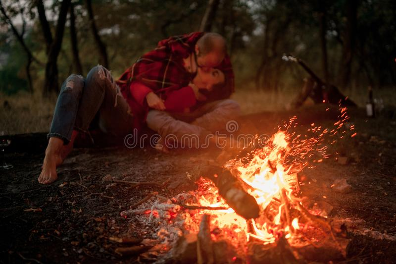 Enamored couple lies, hugs and kisses in forest against background of bonfire flame and sparks. stock photo