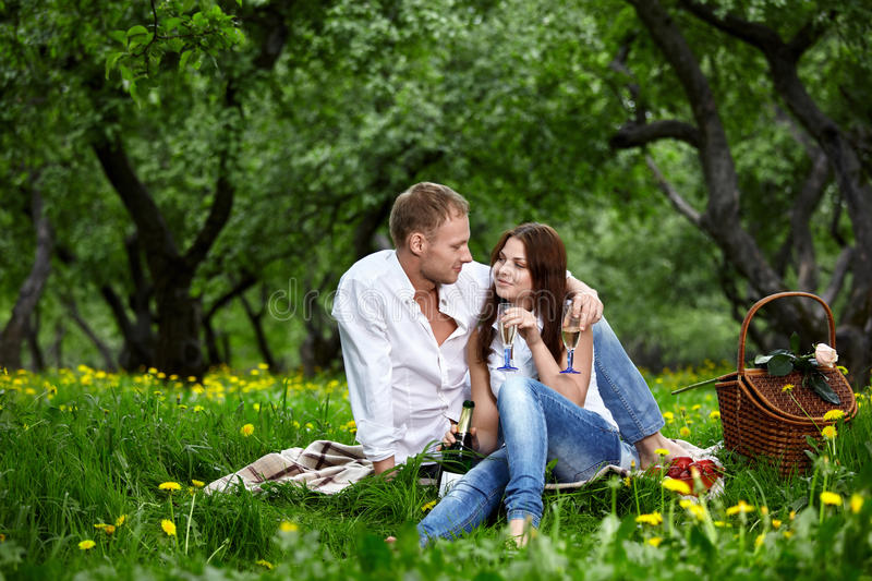 Enamoured couple on picnic. Young enamoured couple on rest in park stock photo