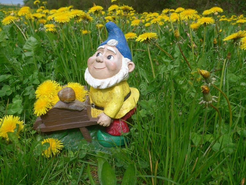 Enano del jard n con la carretilla y caracol en un prado for Enanos jardin