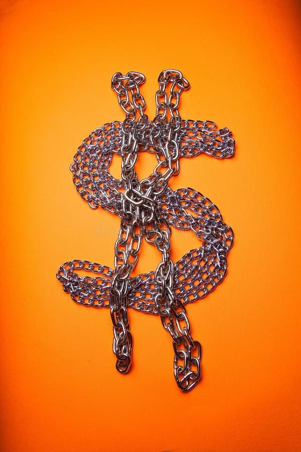 Encadenamientos del dólar en fondo anaranjado imagen de archivo libre de regalías