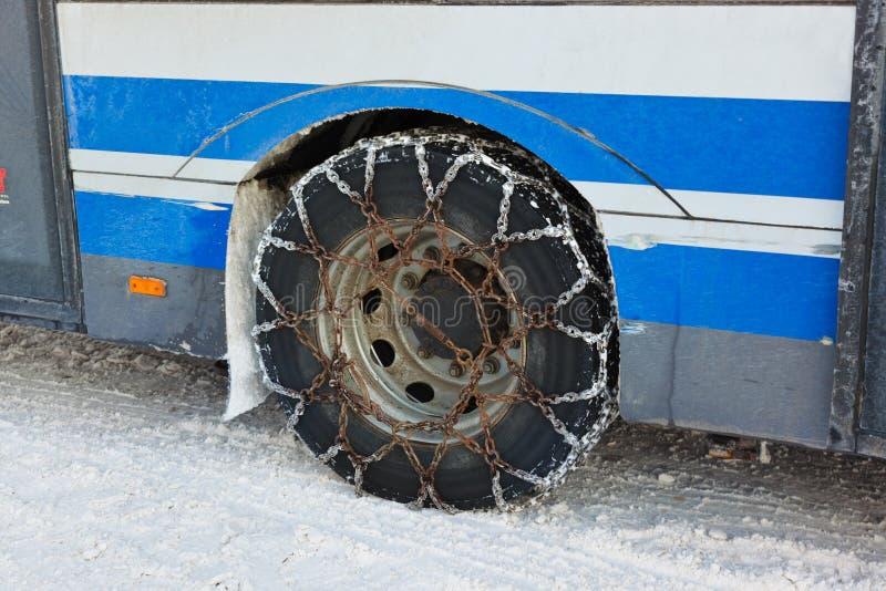 Encadenamientos del invierno de la nieve en el neumático del coche foto de archivo
