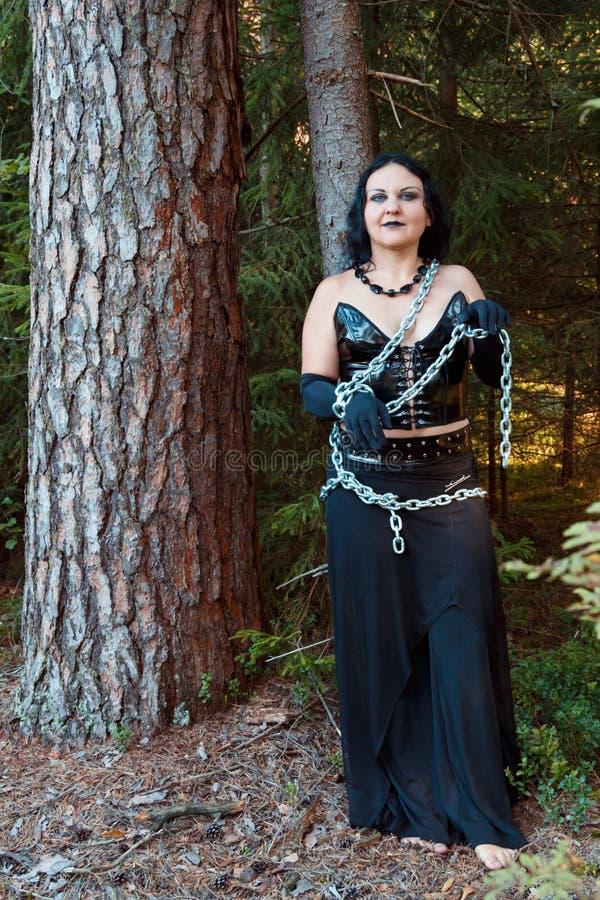Encadenan a una bruja joven en ropa negra a un árbol Víspera de Todos los Santos imagenes de archivo