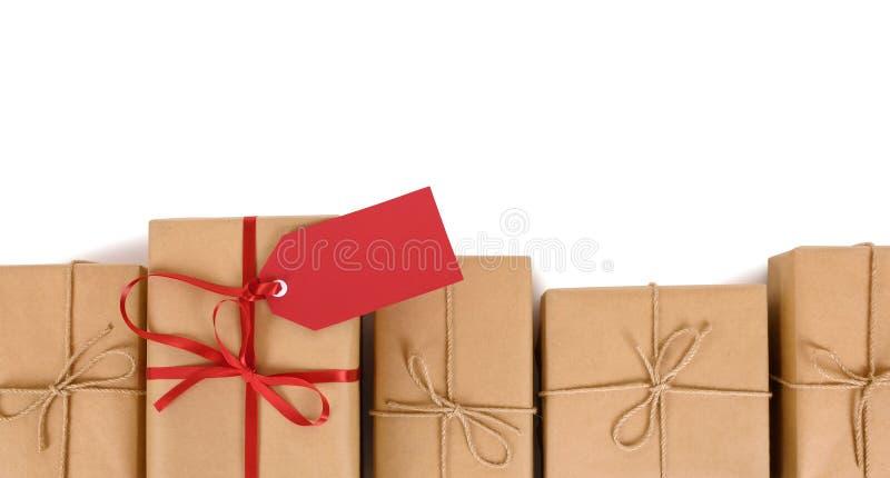 Encadrez la rangée des colis de papier brun, une unique avec l'arc rouge de ruban et l'étiquette de cadeau photos libres de droits