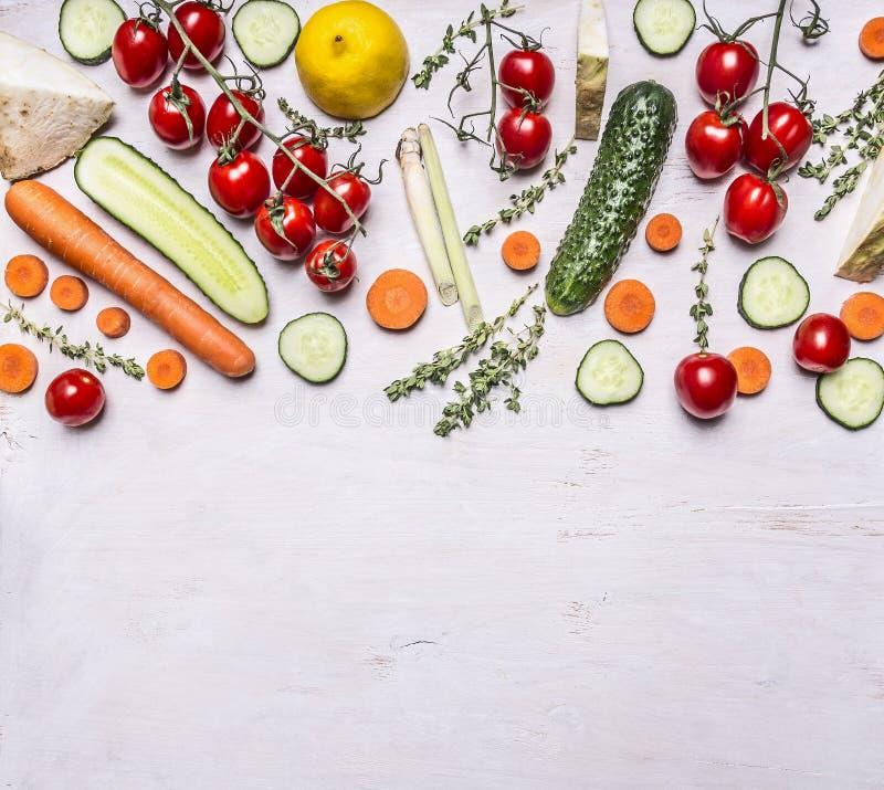 Encadrez les divers fruits frais et les herbes de légumes assaisonnant la nourriture végétarienne sur l'endroit rustique en bois  images libres de droits