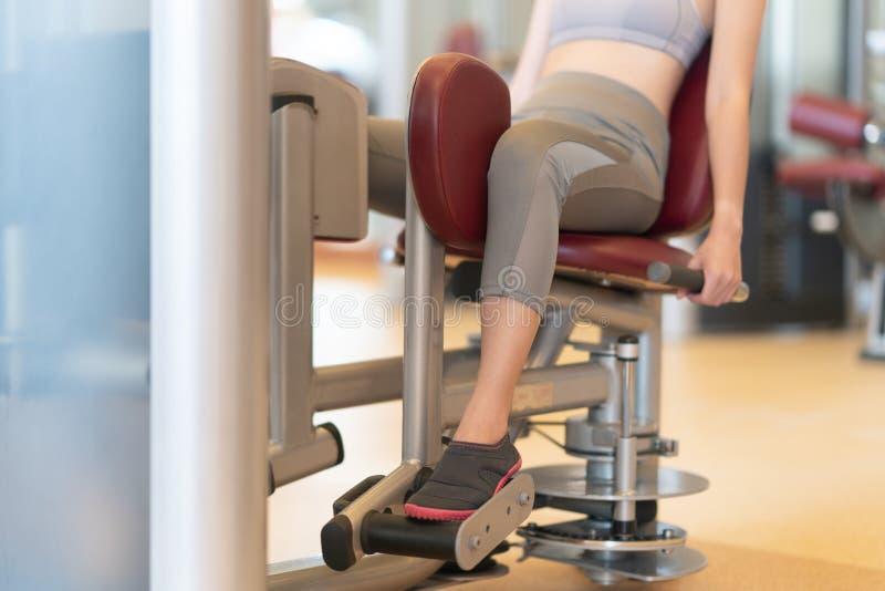 Encaixe a mulher usando uma máquina de pesos para as pernas na academia foto de stock
