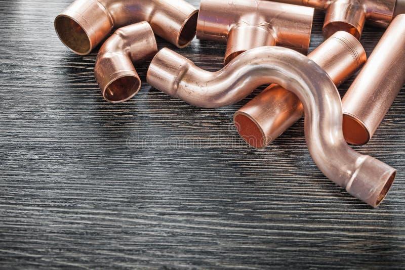 Encaixes de tubulação de cobre da água do encanamento na placa de madeira fotografia de stock royalty free