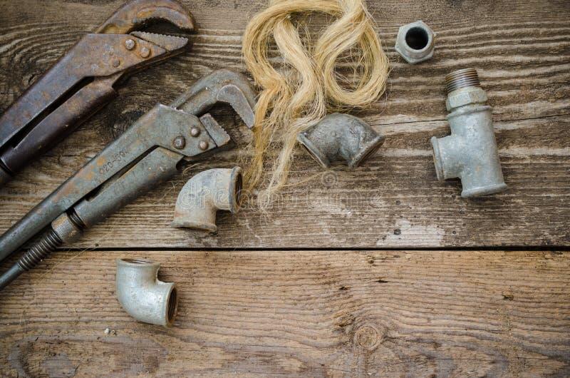 Encaixes do encanamento da chave de tubulação na placa de madeira imagens de stock