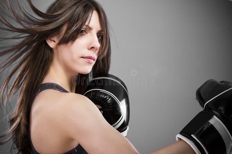 Um lutador fêmea novo e apto 'sexy' que levanta no combate levanta fotos de stock royalty free