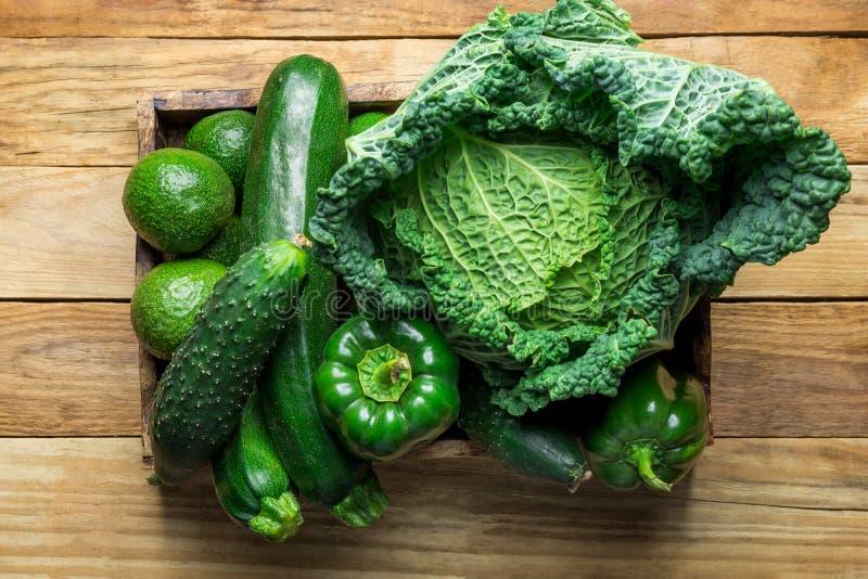 Encaixote com os abacates verdes orgânicos frescos das pimentas de Bell dos pepinos do abobrinha do couve-de-milão dos vegetais n imagem de stock royalty free